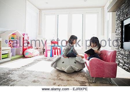 Sisters using digital tablet in playroom - Stock Photo
