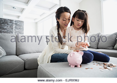 Mother and daughter counting coins from piggy bank - Stock Photo
