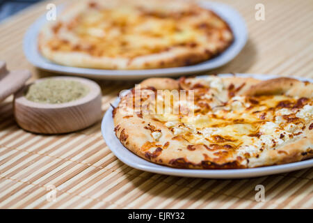 Hot Tasty bread cake with feta cheese made in fire furnace of bakery - Stock Photo