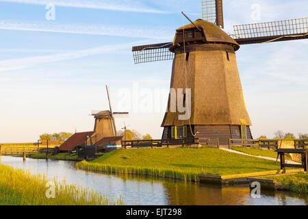 Traditional Windmills beside a Canal, Schermerhorn, North Holland, Netherlands - Stock Photo