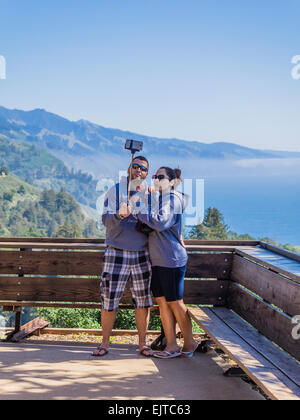 A young adult couple on vacation take a self portrait using a selfie stick with their smartphone in Big Sur, California. - Stock Photo