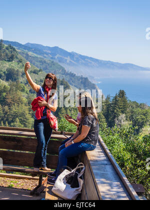 A young female takes a selfie with her smartphone with the coastline of the Pacific Ocean and the mountains at Big - Stock Photo