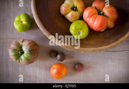 Variety of heirloom tomatoes in a rustic bowl and on a light wood surface. - Stock Photo