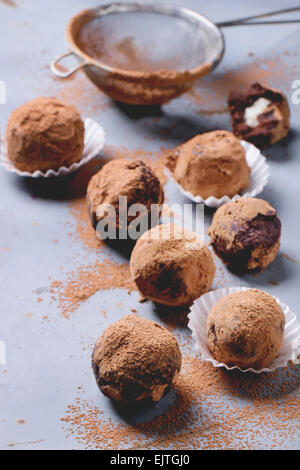 Homemade chocolate truffles with marzipan and cocoa powder over gray matal surface.