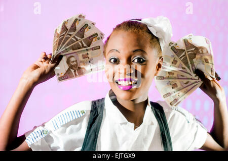 Kenyan woman with Kenyan 100 shilling notes in studio setting - Stock Photo