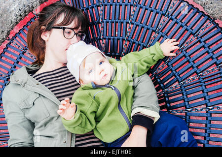 Portrait of baby girl lying with mother on round swing - Stock Photo