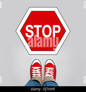 Stop Concept, Young Teenage Person in Red Sneakers Standing in Front of Stop Traffic Sign - Stock Photo