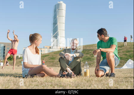 Friends sitting on grassy field in park against Turning Torso - Stock Photo