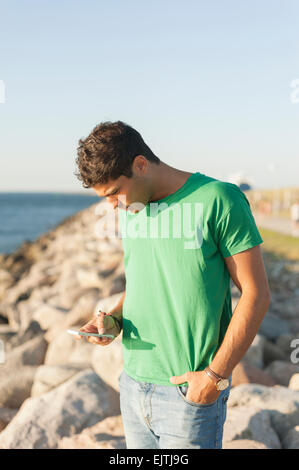 Young man using mobile phone while sitting on rocky shore - Stock Photo