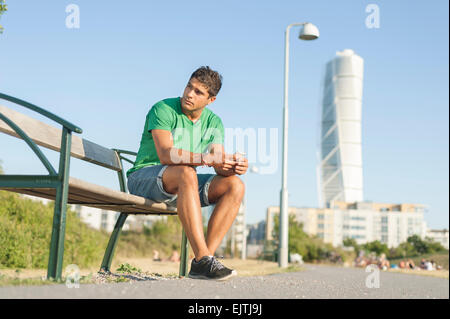 Full length of young man holding mobile phone while sitting on bench in city - Stock Photo