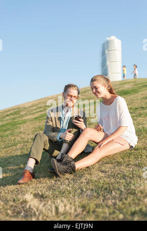 Happy couple using cell phone sitting on grassy hill in city - Stock Photo