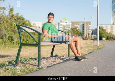 Full length portrait of young man sitting on bench by street in city - Stock Photo