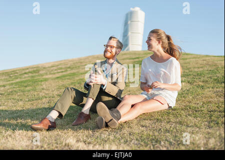 Happy couple sitting on grassy hill in city - Stock Photo