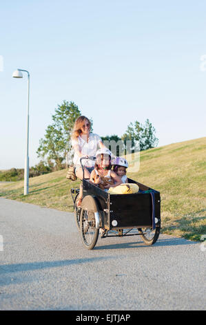 Happy woman riding bicycle with children in cart on street - Stock Photo