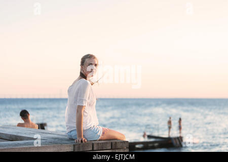 Young woman sitting on pier by sea against clear sky - Stock Photo