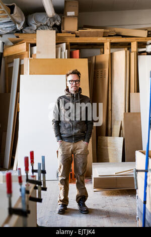 Portrait of confident carpenter standing with hands in pockets at workshop - Stock Photo