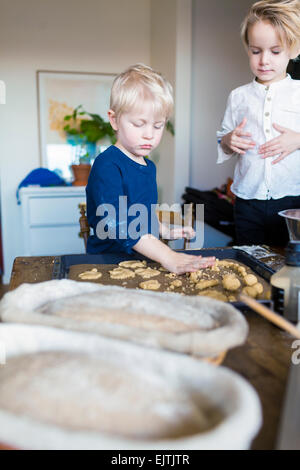 Brothers baking cookies at home - Stock Photo