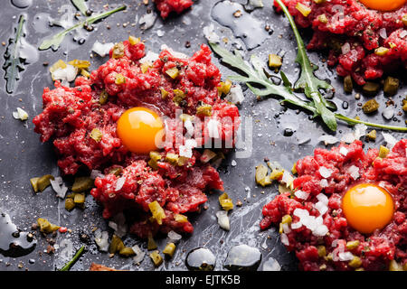 Beef tartare with pickled cucumber and fresh onion on dark marble background close-up - Stock Photo
