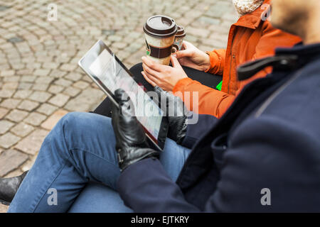 Midsection of man and woman with digital tablet and disposable coffee cups on sidewalk - Stock Photo