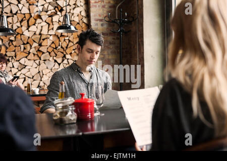 Man with female friends reading menu at table in restaurant - Stock Photo