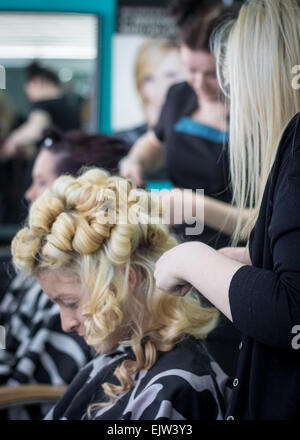 Hairdressers styling two female models in a hair salon for a fashion show,with the one in the foreground having - Stock Photo