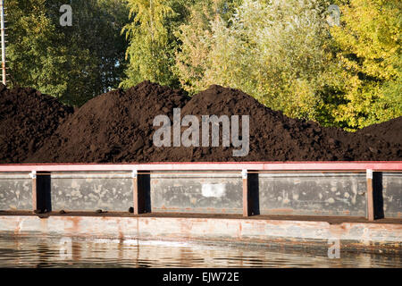 Brown coal loaded on an barge in Germany - Stock Photo