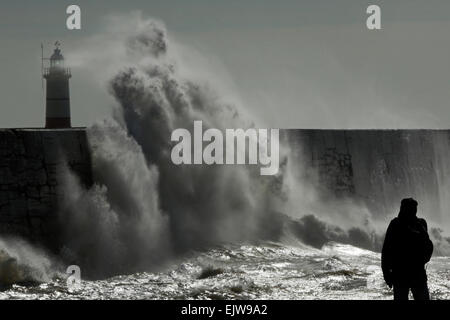 A man watches as waves crash against the harbour wall at Newhaven in East Sussex, UK - Stock Photo