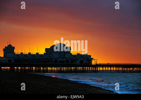 Red sky in the morning as the sun rises behind Southsea Pier at Portsmouth in Hampshire - Stock Photo