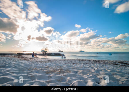 Isla Mujeres, Mexico - April 21, 2014: long exposure of tourists enjoying sunset on famous Playa del Norte beach - Stock Photo