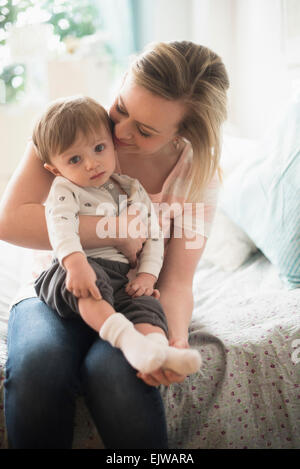 Mother sitting with little son (2-3 years) on bed