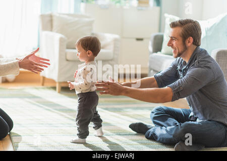 Happy parents helping little son (2-3 years) walking in living room - Stock Photo