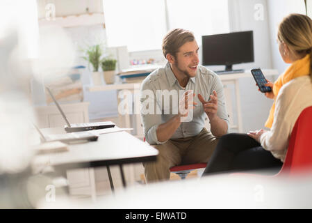 Young man and woman discussing at desk in office - Stock Photo