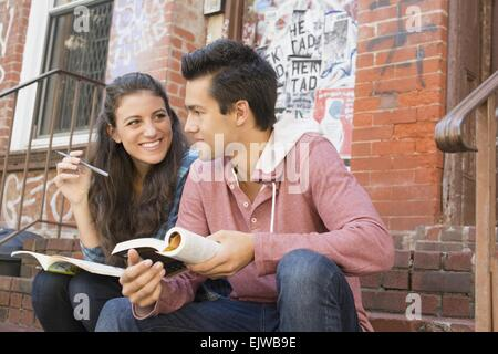 USA, New York State, New York City, Brooklyn, Young couple reading book and doing crossword - Stock Photo