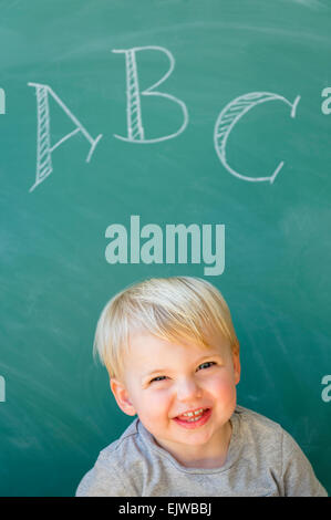 Boy (2-3) smiling in front of blackboard with letters ABC written on it - Stock Photo