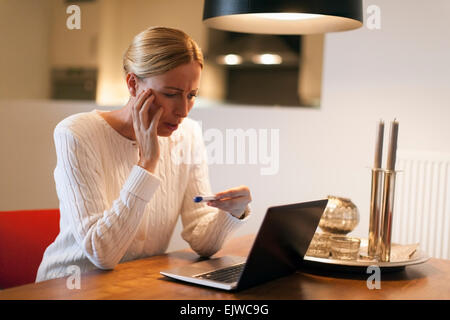 Woman using laptop and looking at pregnancy test - Stock Photo