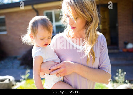 Mother and daughter (12-17 months) in backyard - Stock Photo
