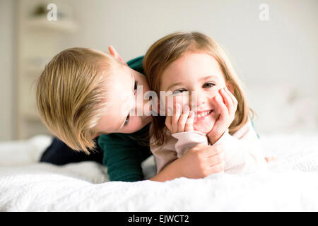 Siblings (2-3, 4-5) whispering in bedroom - Stock Photo
