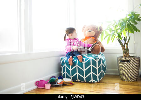 Girl (4-5) sitting with teddy bear on bean bag - Stock Photo