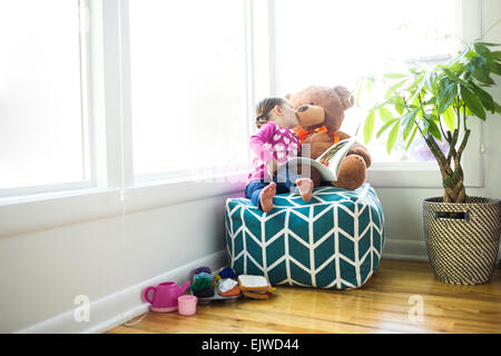 Girl (4-5) kissing her teddy bear on bean bag - Stock Photo
