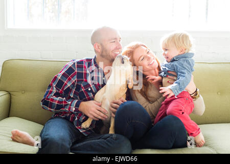 Family with son (2-3) and pug on sofa - Stock Photo