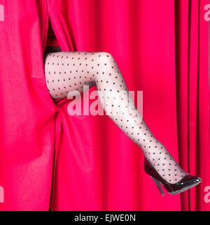 Womans leg wearing black spotted tights appearing through a red curtain - Stock Photo