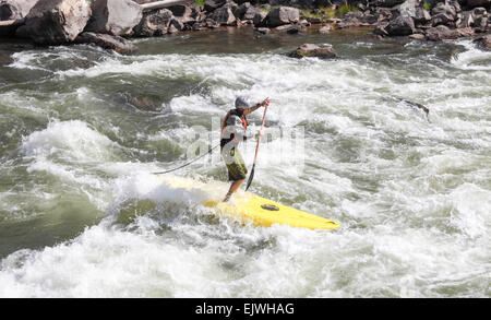 Man standing on board paddles through rapids in Glenwood Canyon - Stock Photo