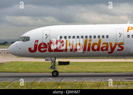 Jet2holidays branded aircraft taxiing towards the terminal at Manchester airport shortly after landing. - Stock Photo
