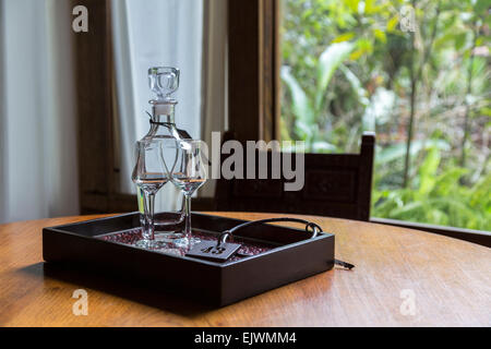 Peru, Machu Picchu Pueblo.  Pisco Brandy in Decanter with Glasses and Room Key. - Stock Photo