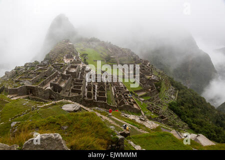 Peru, Machu Picchu.  Early Morning Clouds Engulf the Ruins. - Stock Photo