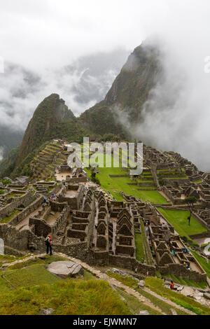 Peru, Machu Picchu, Early Morning Clouds.  Uña Picchu on left, Huayna Picchu in Clouds on Right. - Stock Photo