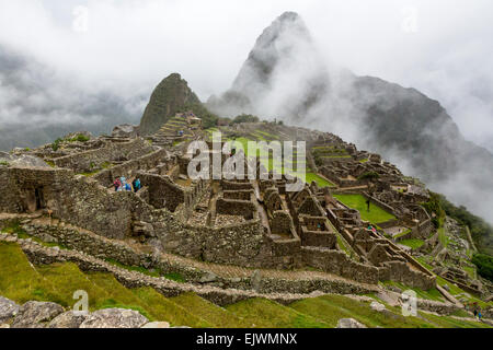 Peru, Machu Picchu.  Early Morning Clouds Lifting.  Huayna Picchu in Background. - Stock Photo