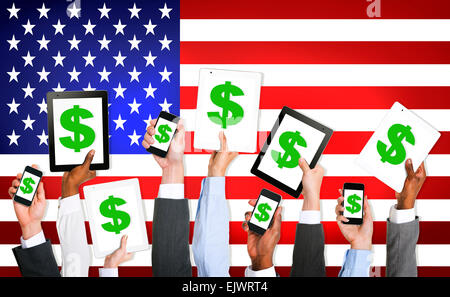 Multi-Ethnic Group Of Business People Holding Technology Devices With A Dollar Sign On A Screen And American Flag - Stock Photo