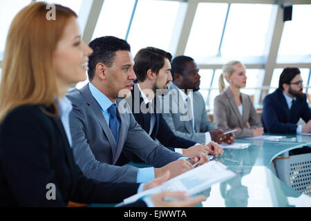 Row of serious business people attending seminar - Stock Photo