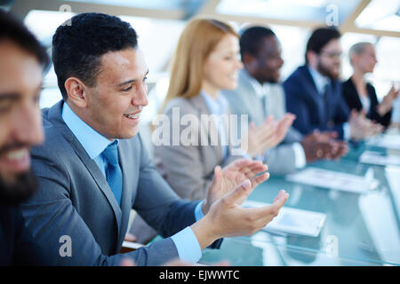 Happy business people applauding to speaker at seminar - Stock Photo